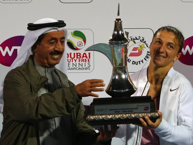 Italian tennis player Sara Errani (R) and Sheikh Hasher bin Maktoum, head of the UAE tennis federation, pose with the winner's trophy after Errani beat Czech player Barbora Strycova in the semi-final WTA tennis match of the Dubai Duty Free Tennis Championships, on February 20, 2016. Sara Errani (ITA) beat Barbora Strycova (CZE) 6-0, 6-2