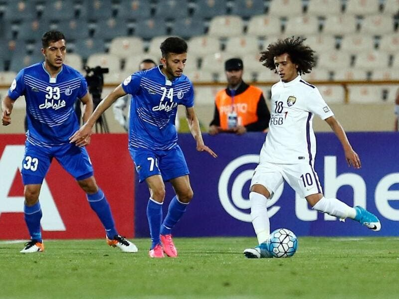 Esteghlal's Mojtaba Haghdust (C) fights for the ball agaisn al-Ain's Omar Abdulrahman (R) during the 2017 AFC Champions League round 16 football match between Iran's Esteghlal FC and UAE's Al-Ain (UAE) FC at the Azadi Stadium in Tehran on May 22, 2017.