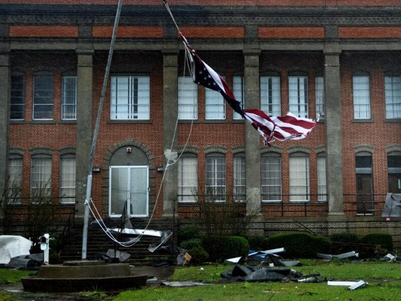 An American flag is torn in front of a school during Hurricane Michael October 10, 2018 in Panama City, Florida. (Brendan Smialowski / AFP)