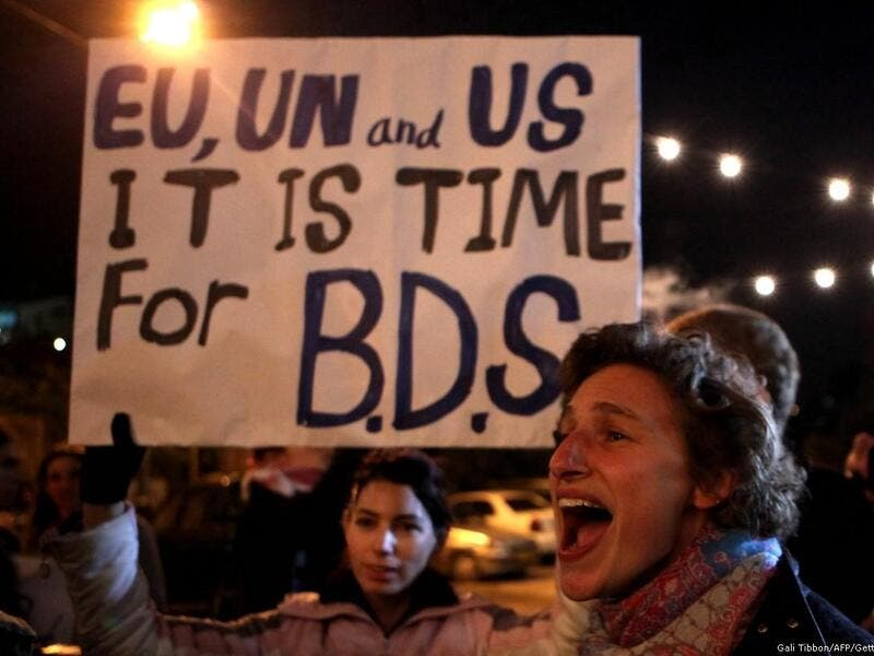 Demonstrators hold a placard urging the international community to support the Boycott, Divestment, and Sanctions (BDS) campaign. (AFP/ File Photo)