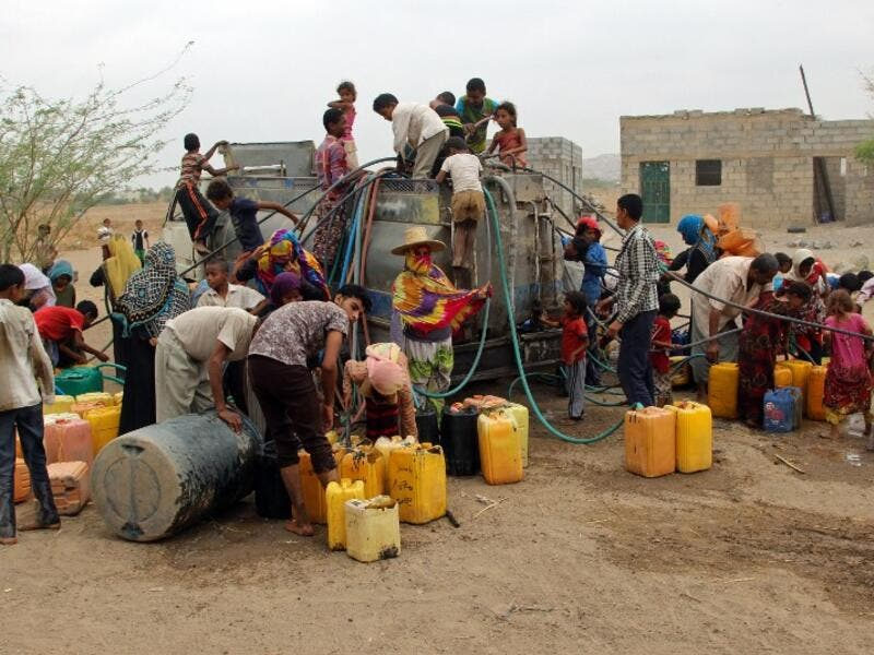 Yemenis collect water from a donated source amid an ongoing wide spread disruption of water supplies in an impoverished coastal village on the outskirts of the Yemeni port city of Hodeidah, on April 17, 2017. (AFP/Stringer)