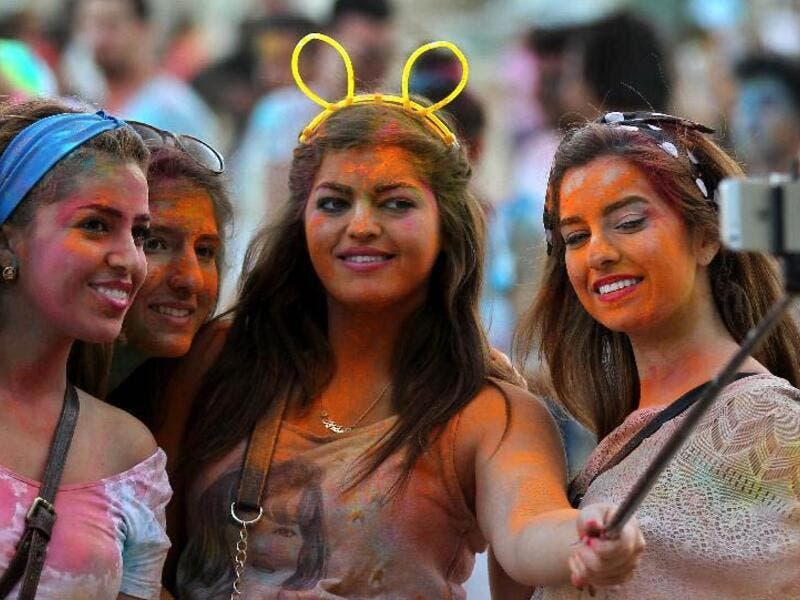 People take part in the International Color Festival in Amman, Jordan, on Aug 2, 2014. (Xinhua)