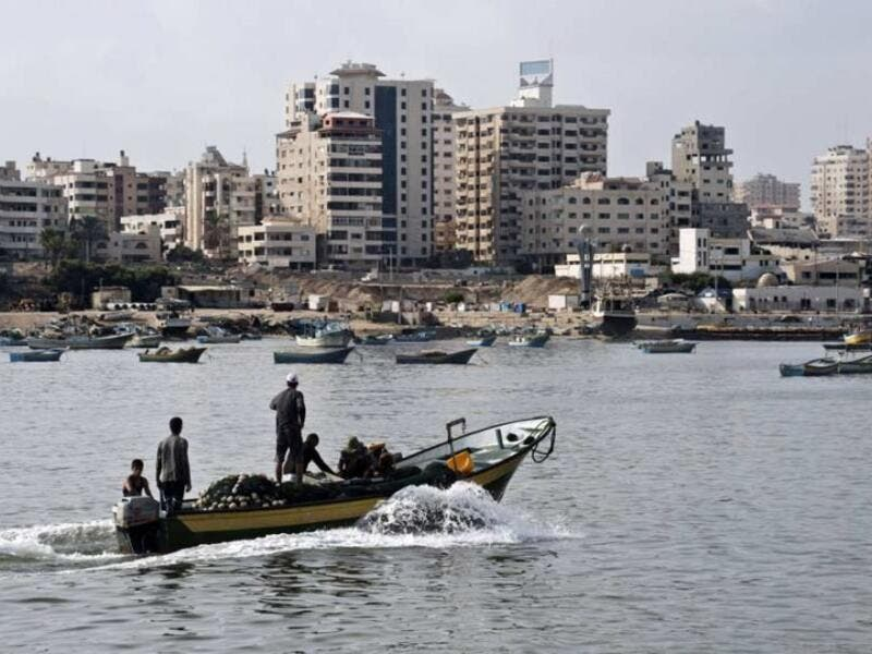 Fishermen ride a small boat into the harbour on August 18, 2014 in Gaza City. (ROBERTO SCHMIDT/AFP)
