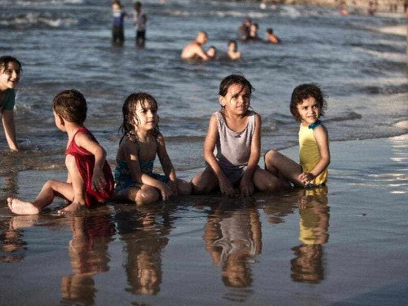 Children play in the water in Gaza City (AFP/File Photo)