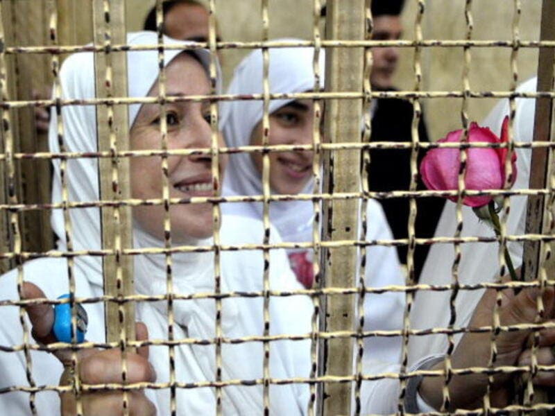 Egyptian women members of the Muslim Brotherhood hold roses as they stand in the defendants' cage dressed in prison issue white during their trial in at the court in the Egyptian Mediterranean city of Alexandria on December 7, 2013. [Getty Images]