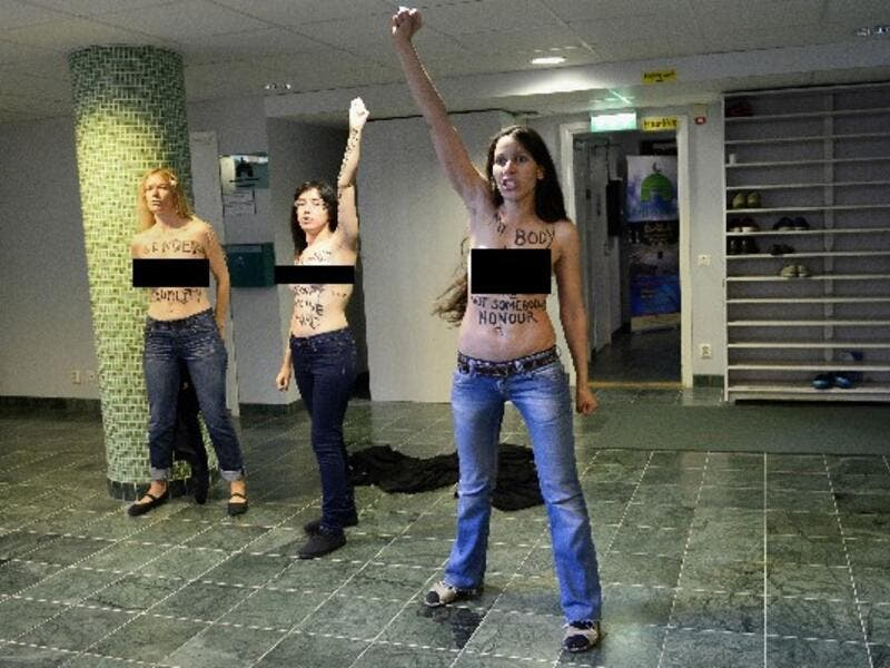 Egyptian activist Aliaa Elmahdy (C) and other members of feminist group FEMEN stage a topless protest  inside a Mosque in Stockholm, Sweden on Saturday (AFP)