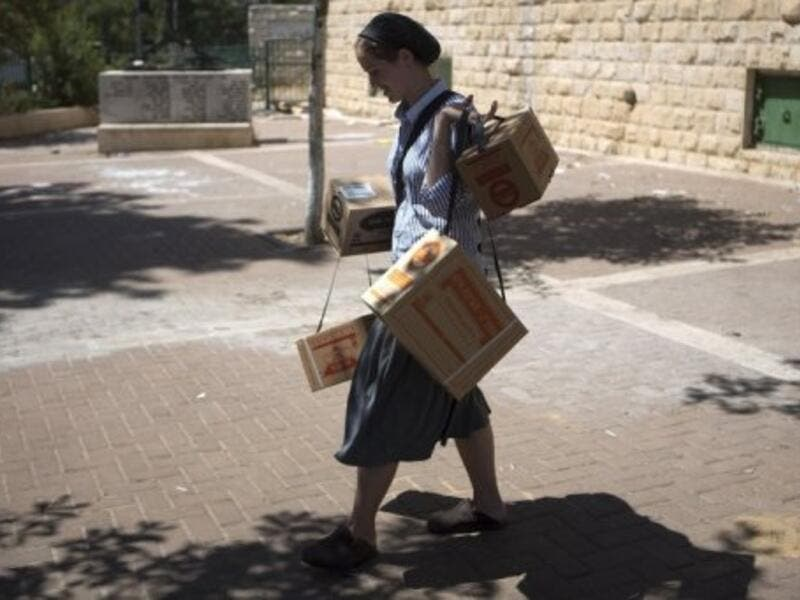 An Israeli woman carries gas masks as she leaves the distribution centre in Jerusalem on August 26, 2013 (AFP)