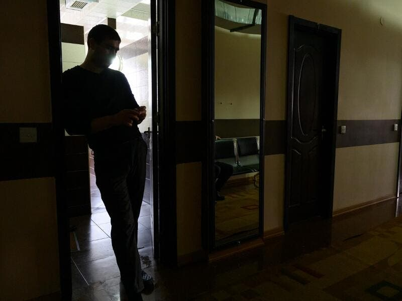 A man stands in a corridor at the Sehirli Naftalan Health Center, some 300 kilometres (186 miles) from capital Baku, on March 21, 2019. Immersed up to her neck in crude oil, a Russian woman suffering from joint disease smiles in delight, confident that the treatment at a spa in northwestern Azerbaijan will cure her painful condition.  Mladen ANTONOV / AFP