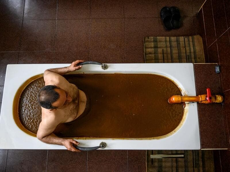 A man bathes in a tub filled with Naftalan crude oil during a treatment session at Sehirli Naftalan Health Center, some 300 kilometres (186 miles) from capital Baku, on March 21, 2019. Immersed up to her neck in crude oil, a Russian woman suffering from joint disease smiles in delight, confident that the treatment at a spa in northwestern Azerbaijan will cure her painful condition.  Mladen ANTONOV / AFP