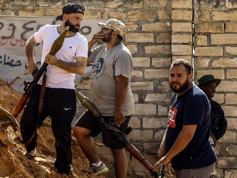 Libyan fighters loyal to the Government of National Accord (GNA) hold rocket-propelled grenade (RPG) launchers as they stand behind a dirt barrier during clashes with forces loyal to strongman Khalifa Haftar south of the capital Tripoli's suburb of Ain Zara, on April 10, 2019. Mahmud TURKIA / AFP