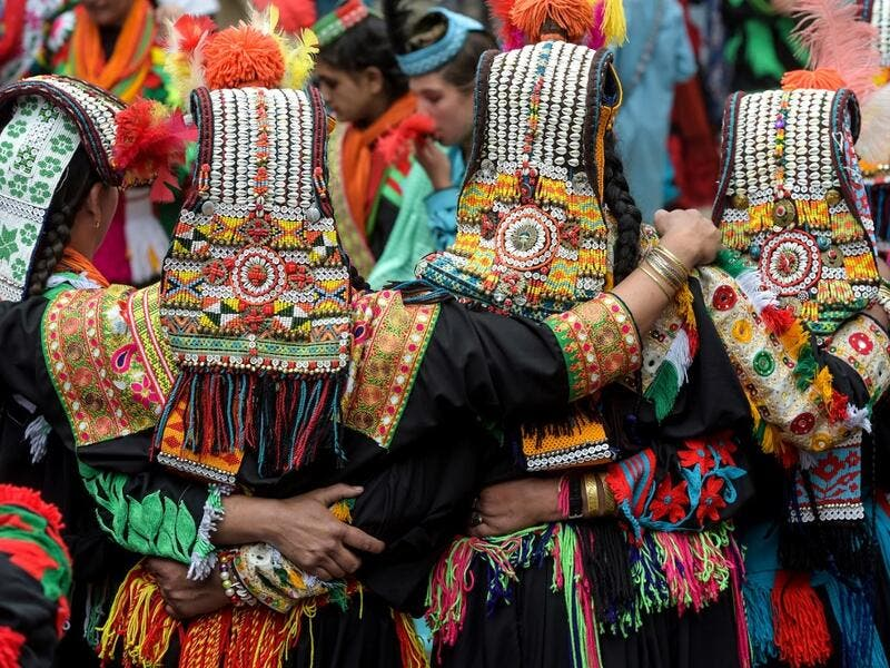 Kalash women wearing traditional dresses dance as they celebrate 'Joshi', a festival to welcome the arrival of spring, at Bumburate village in the mountainous valleys in northern Pakistan.  AAMIR QURESHI / AFP