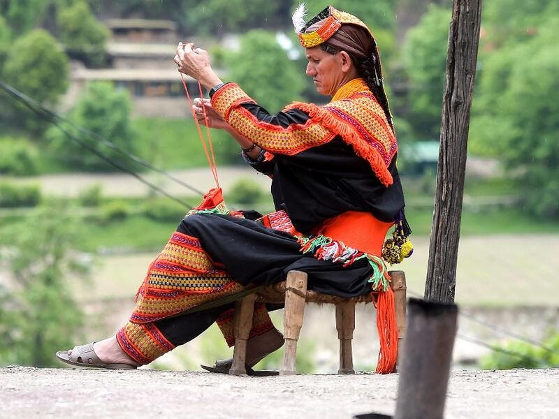 In this picture a Kalash woman wearing a traditional dress knits clothes outside her house after celebrating 'Joshi', a festival to welcome the arrival of spring, at Bumburate village in the mountainous valleys in northern Pakistan. AAMIR QURESHI / AFP