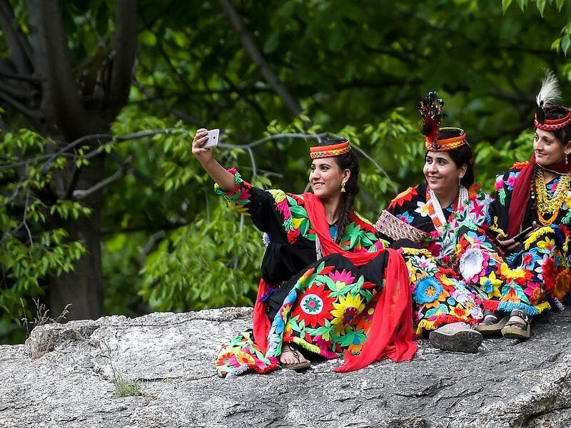 In a remote valley in Pakistan dozens of Kalash minority women dance to celebrate spring's arrival -- but as a gaggle of men scramble to catch them on camera, the community warns an influx of domestic tourists is threatening their unique traditions.  AAMIR QURESHI / AFP