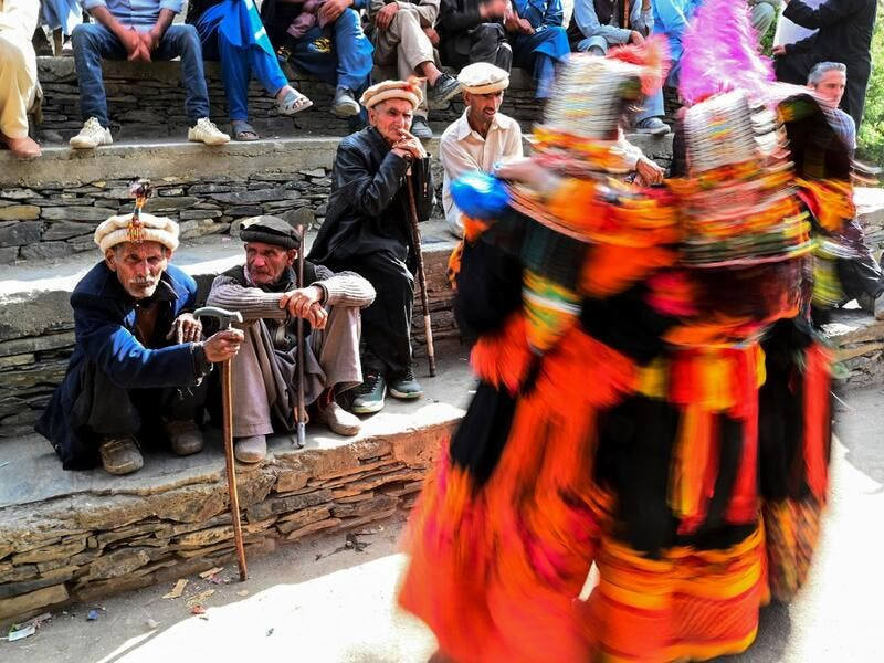 In this picture  Kalash elderly men watch women dancing as they celebrate 'Joshi', a festival to welcome the arrival of spring, at Bumburate village in the mountainous valleys in northern Pakistan.  AAMIR QURESHI / AFP