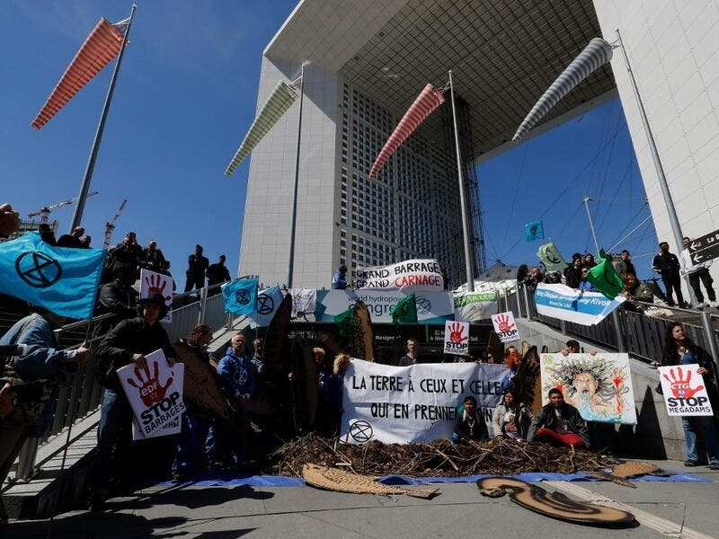 Activists of 'Extinction Rebellion' (XR) and NGO 'Planete Amazone' stage a protest against large hydroelectric dams in front of the Grande Arche de La Defense in Puteaux, northwest of Paris, on May 14, 2019, on the occasion of the 2019 World Hydropower Congress. The congress is held in Paris from May 14 to 16. FRANCOIS GUILLOT / AFP
