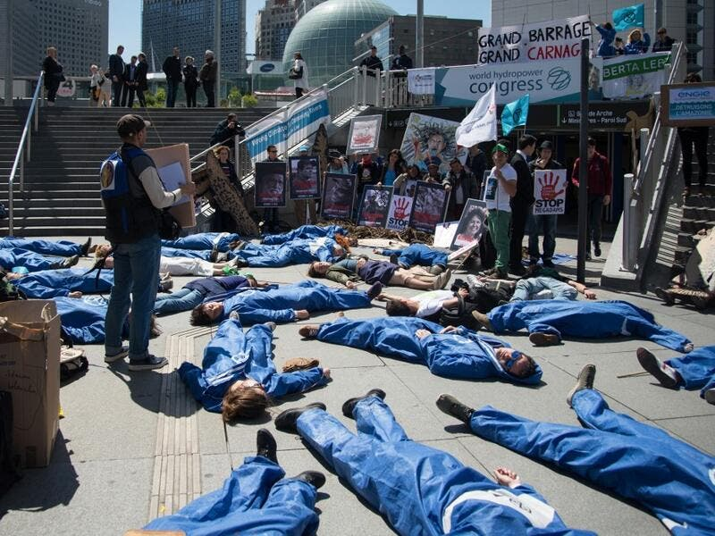 "Activists of 'Extinction Rebellion' (XR) and NGO 'Planete Amazone' lie on the ground to stage an action called ""die-in"" to highlight the risk of the human race becoming extinct as a result of climate change, during a protest against large hydroelectric dams in front of the Grande Arche de La Defense, in Puteaux, northwest of Paris, on May 14, 2019. AFP"