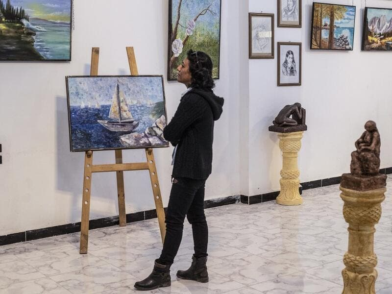 Amal al-Attar, a 37-year-old artist, looks at her artworks on display during an exhibition at the first cultural centre to open since ISIS rule ended in the eastern Syrian city of Raqa on May 1, 2019. DELIL SOULEIMAN / AFP