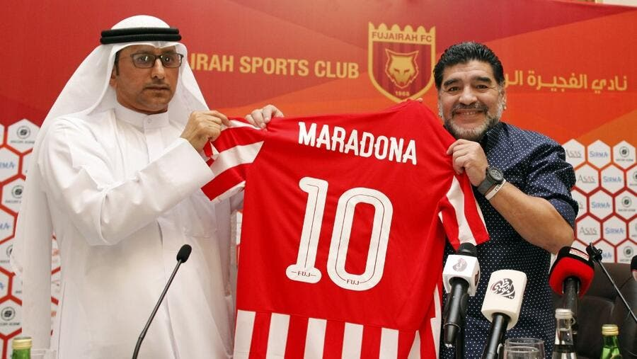 Photo taken on May 14, 2017  Diego Armando Maradona (R) holds a jersey of the football club Fujairah FC, bearing his name, during a press conference where he was announced as the upcoming manager for the team (Photo: AFP)