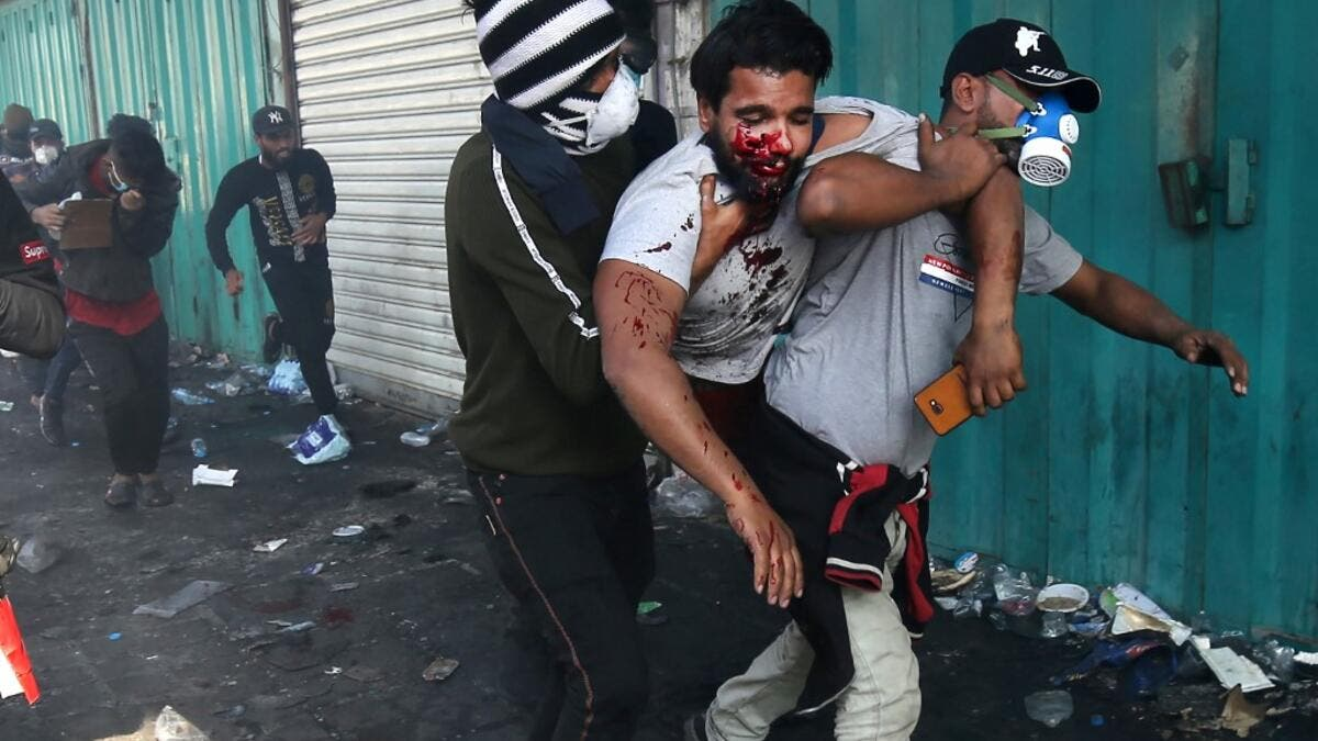 In this file photo taken on November 15, 2019, Iraqis carry a protester wounded after being struck by a tear gas canister amidst clashes with security forces at the capital Baghdad's Khallani square during ongoing anti-government demonstrations. At least 3,000 people who have been maimed in Baghdad and southern Iraq since anti-government protests erupted on October 1, according to the NGO Iraqi Alliance for Disabilities Organisation (IADO). After decades of back-to-back conflicts, Iraq is in the thick of it