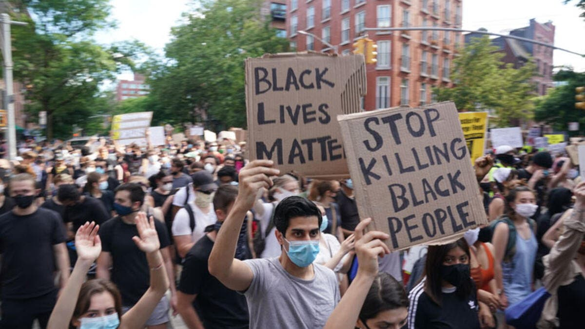 Protesters march and carry signs in the West Village as they demonstrate in outrage over the death of George Floyd, who died while in custody of the Minneapolis police, at a rally on May 30, 2020 in New York. AFP