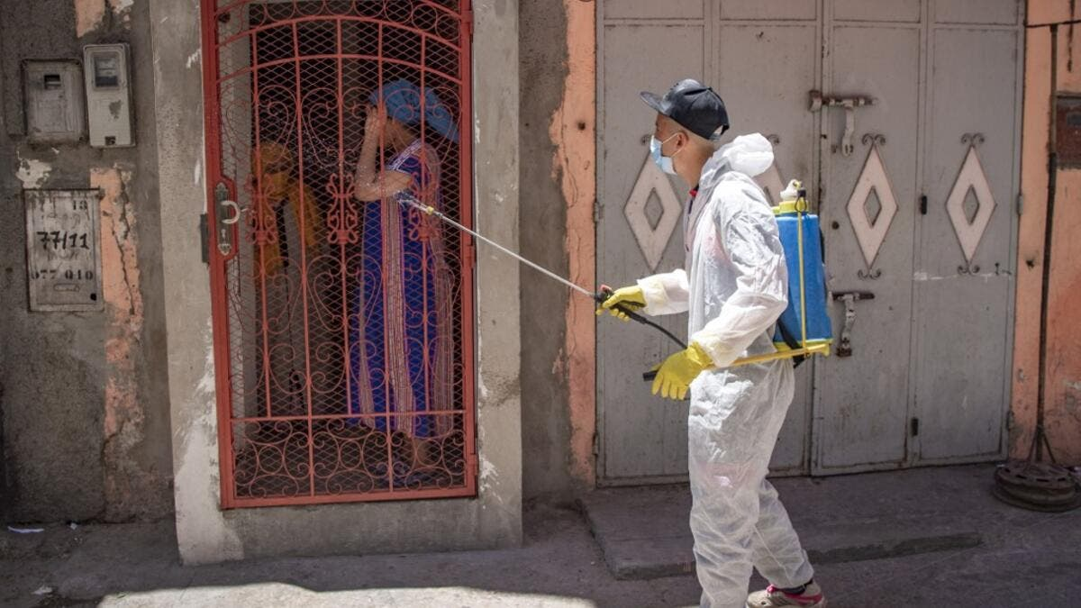 A Moroccan municipal worker disinfects outside a house in a closed street in the southern port city of Safi on June 9, 2020 after Moroccan authorities declared a total lockdown following the discovery of many new COVID-19 coronavirus cases there at a fish canning factory. FADEL SENNA / AFP
