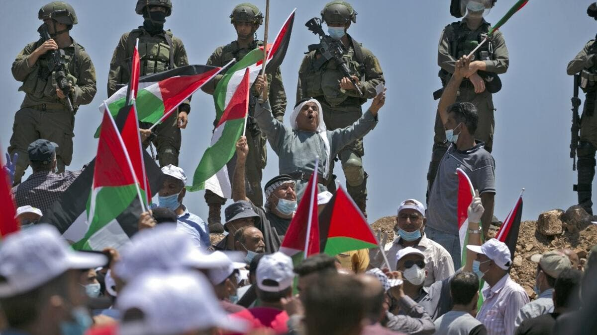 Demonstrators, clad in masks and latex gloves, wave Palestinian flags while Israeli forces stand on guard nearby during a protest against Jewish settlements and Israel's planned annexation of parts of the Israeli-occupied West Bank, in the town of Asira Shamaliya near the West Bank city of Nablus on July 10, 2020. ABBAS MOMANI / AFP