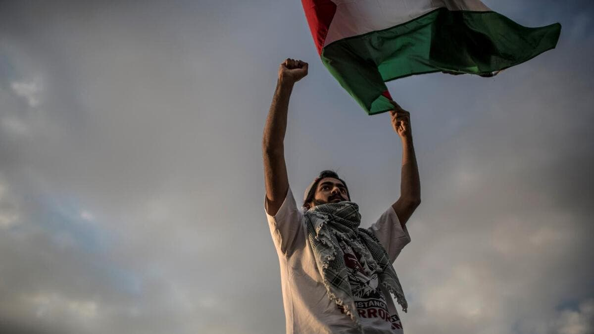 A man waves a Palestinian flag during a protest to mark Nakba Day (AFP)