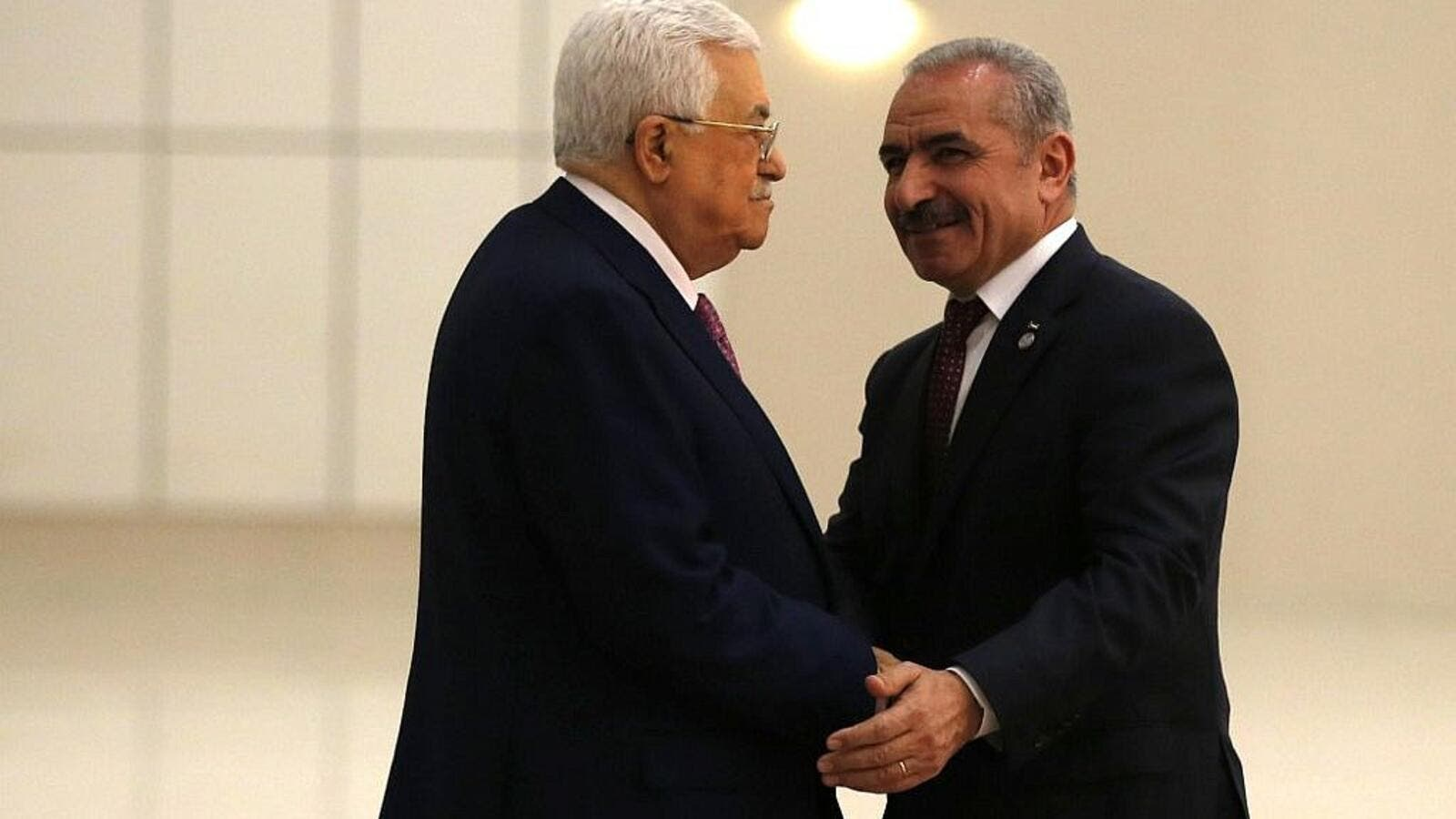 Palestinian Authority President Mahmoud Abbas (L) shakes hands with the prime minister Mohammad Shtayyeh in the West Bank city of Ramallah, on April 13, 2019. (Abbas Momani/AFP)