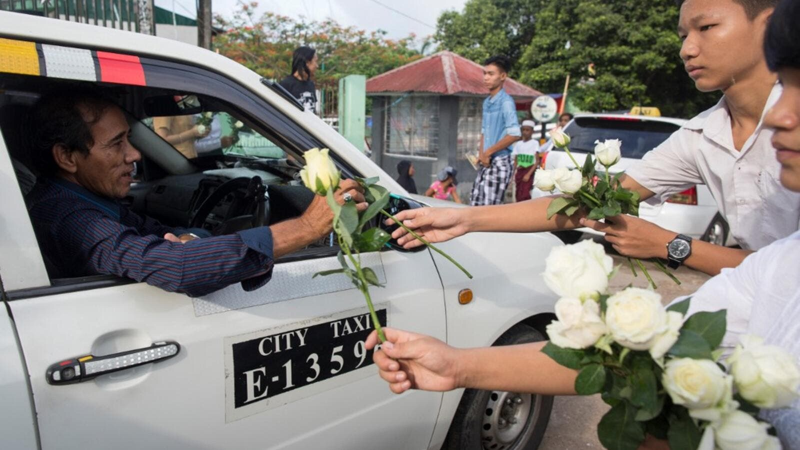 Buddhists give white roses to Muslims as they attend prayers during Eid al-Fitr at Than Lyin township on the outskirts of Yangon on June 5, 2019. (AFP/ File)