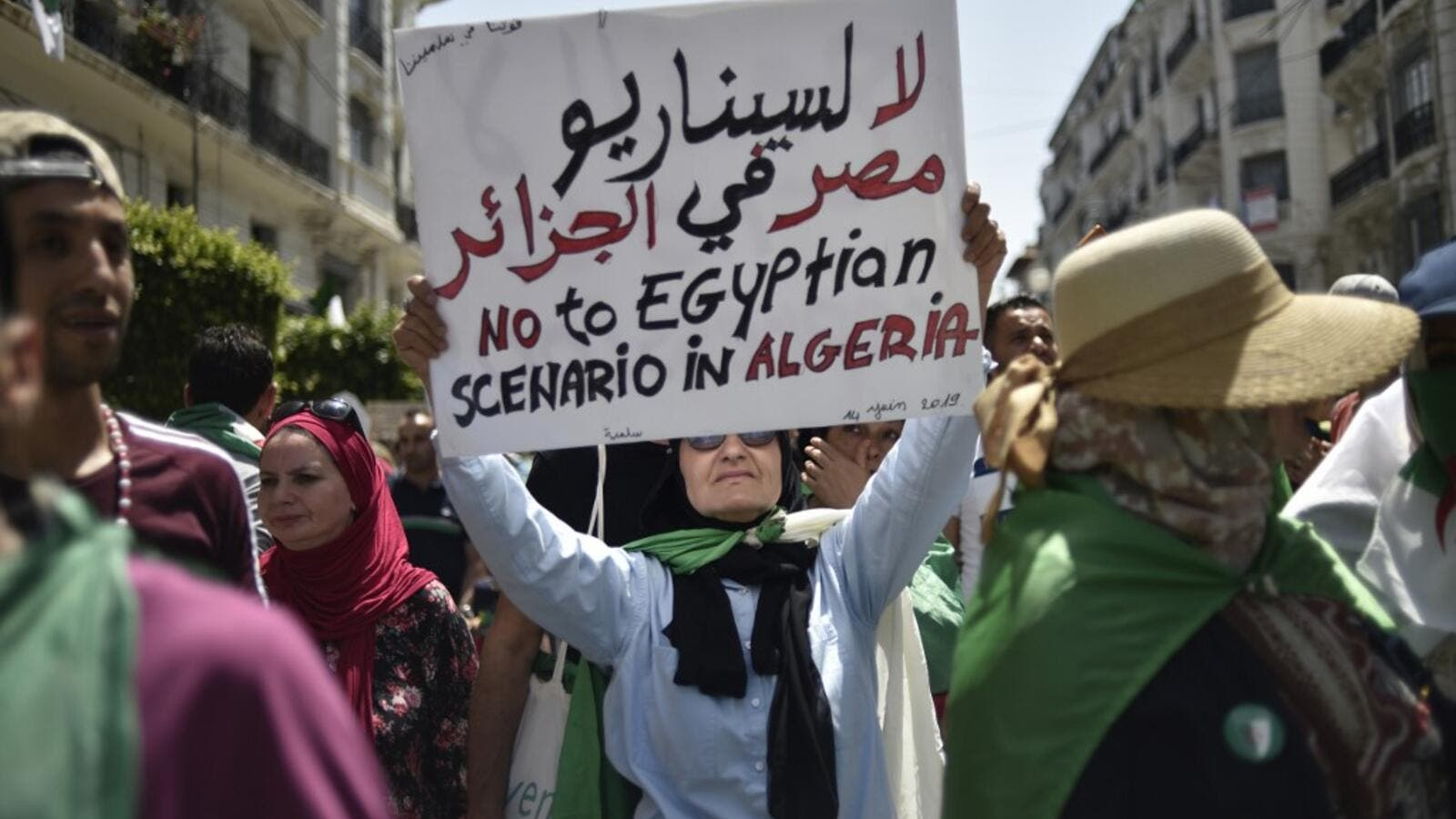 An Algerian woman raises a placard as she takes part in a weekly demonstration in the capital Algiers on June 14, 2019. (AFP/ File Photo)