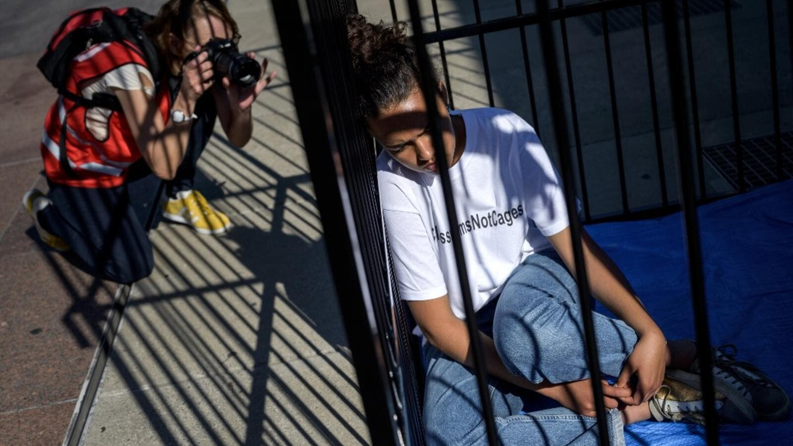 A photographer takes a picture of a teenager sitting in a cage during a protest of international labor groups, civil society and students against the policy of migrant family separation along the US-Mexico border on June 17, 2019 in front of the United Nations offices in Geneva. (FABRICE COFFRINI / AFP)