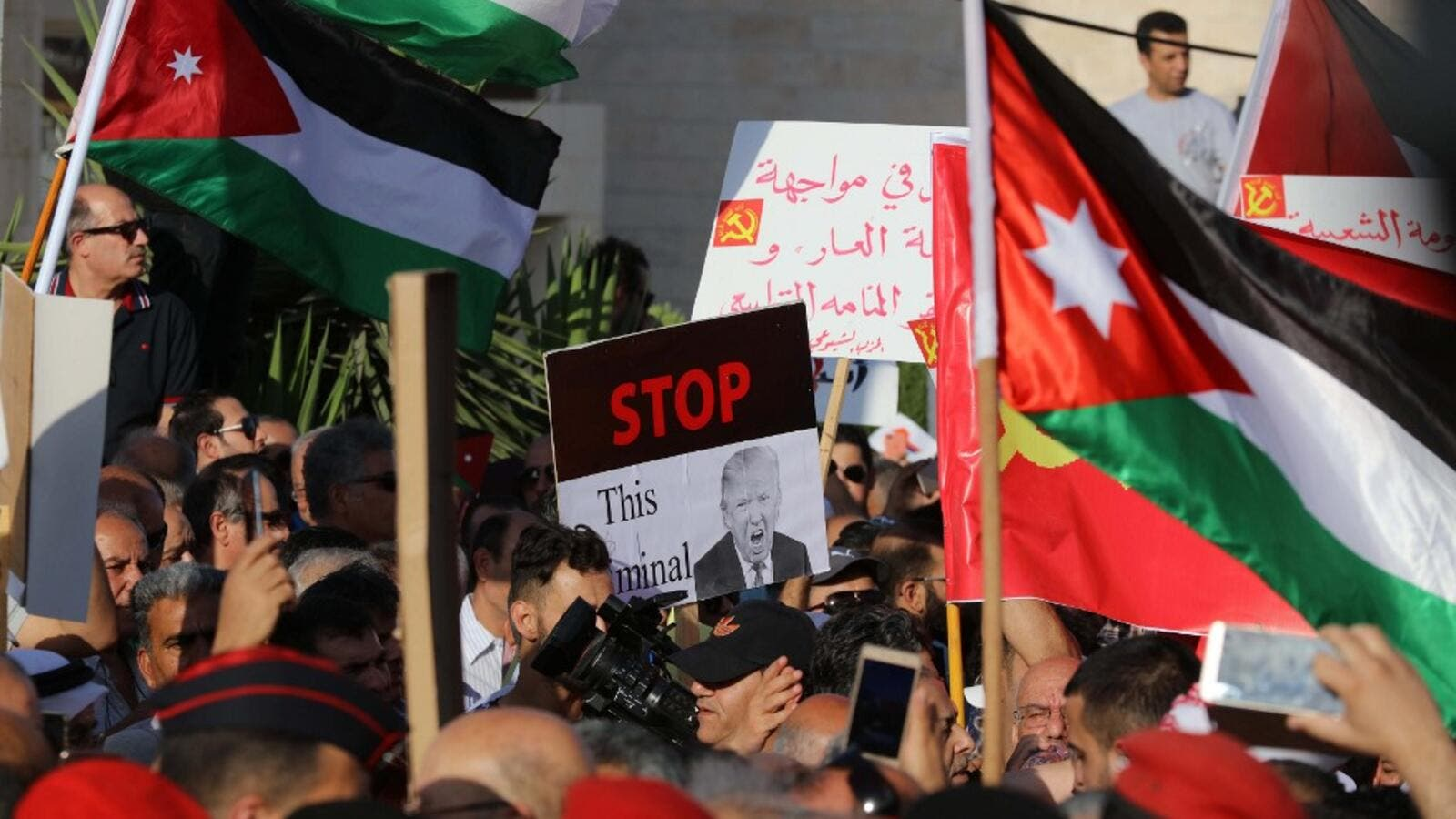 "Protesters hold an anti-Donald Trump signs and Jordanian flags during the ""March of Anger"" demonstration leading to the US embassy headquarters in the Jordanian capital Amman on June 21, 2019, against the US President's ""Deal of the Century"" and the US-led Middle East economic conference in Bahrain. (Khalil MAZRAAWI / AFP)"