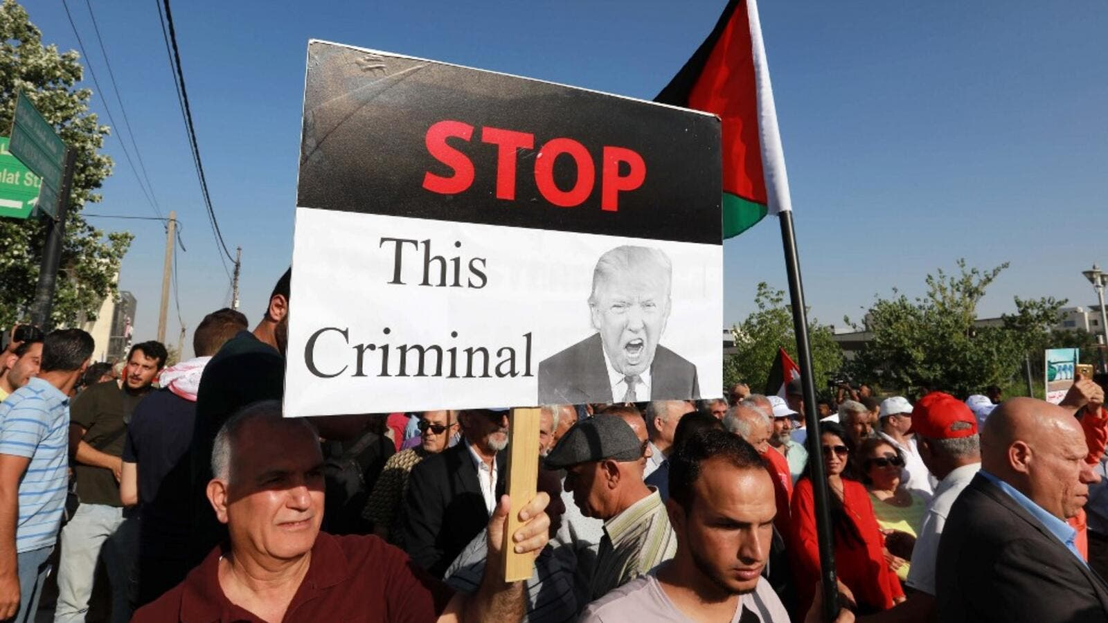"A protester holds an anti-Donald Trump sign as he marches with others during the ""March of Anger"" demonstration leading to the US embassy headquarters in the Jordanian capital Amman on June 21, 2019, against US President Donald Trump's ""Deal of the Century"" and the US-led Middle East economic conference in Bahrain.  (Khalil MAZRAAWI / AFP)"