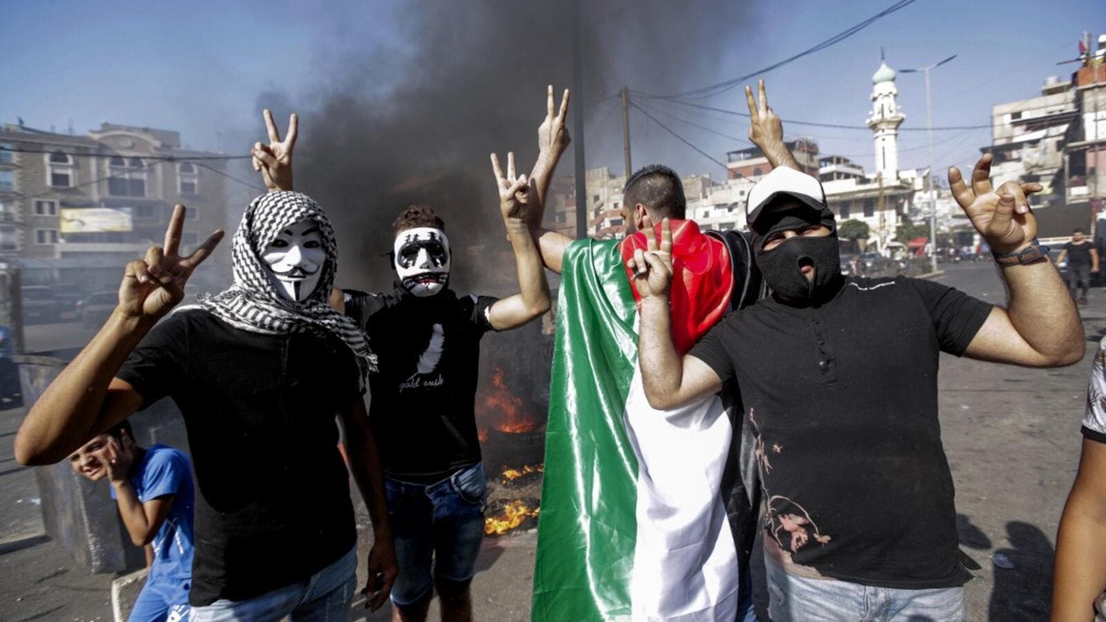 Masked protesters flash the victory gesture as they block the main road outside the Palestinian refugee camp of Burj al-Barajneh, south of the Lebanese capital Beirut, on July 16, 2019. (AFP/ File Photo)