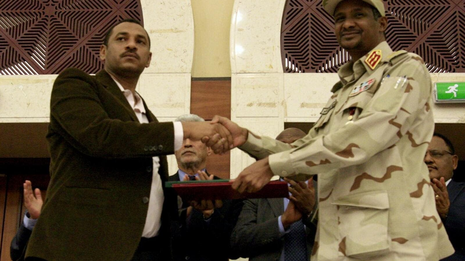 Sudanese deputy chief of the ruling miliary council Mohamed Hamdan Dagalo (R) and protest movement Alliance for Freedom and Changes leader Ahmad al-Rabiah shake hands after inking an agreement before African Union and Ethiopian mediators in Khartoum early on July 17, 2019. (AFP)