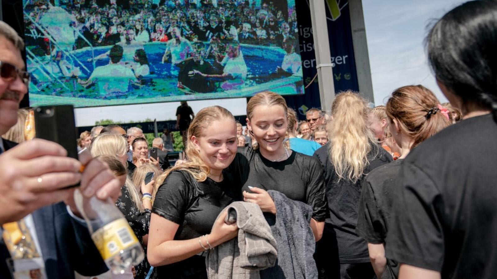 Jehovah's Witnesses react after receiving the baptism during a group baptism event during an international convention at Broendby Stadium on July 20, 2019 in Copenhagen.  Ida Marie Odgaard / Ritzau Scanpix / AFP