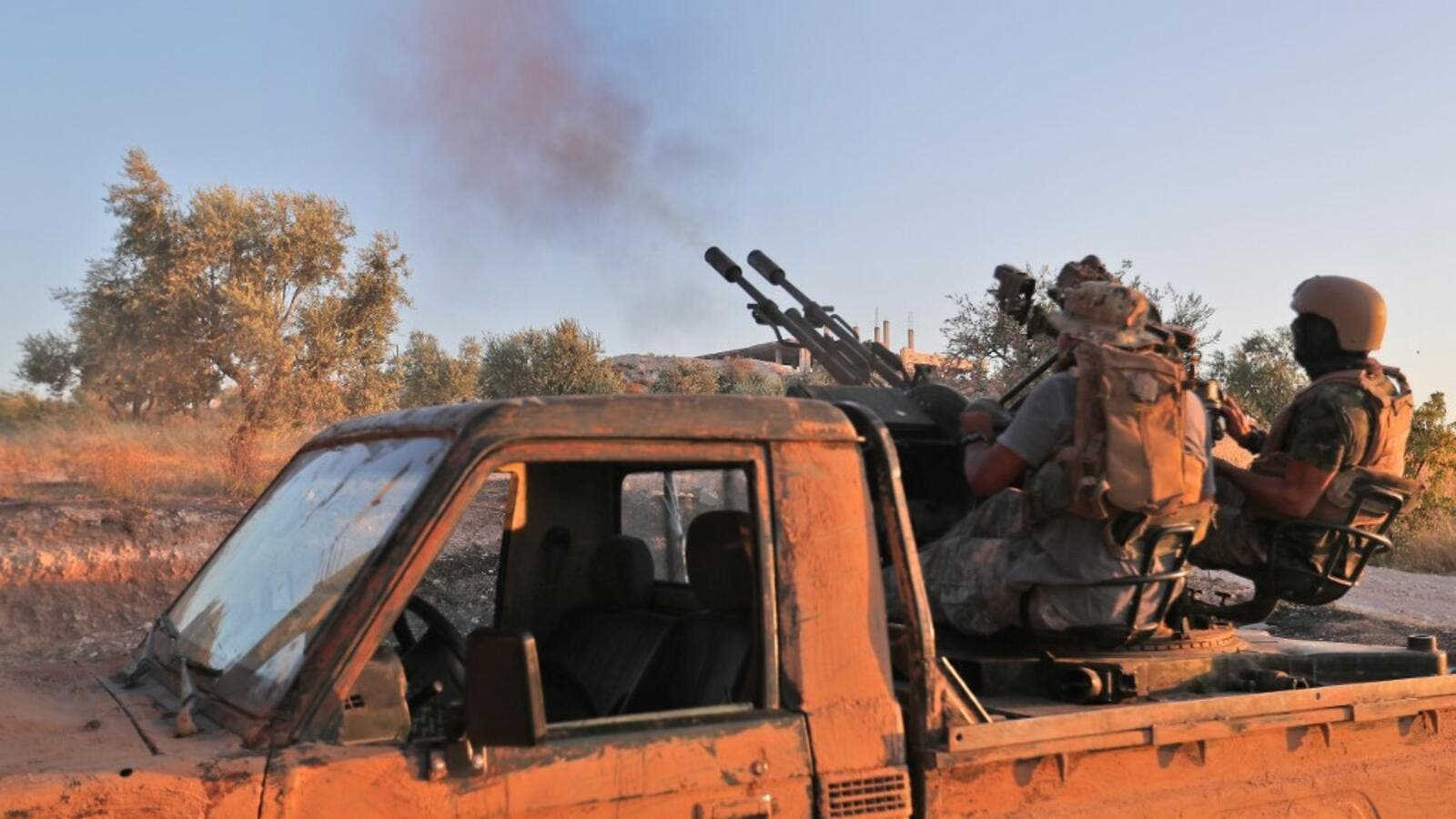 Fighters from the former al-Qaeda Syrian affiliate Hayat Tahrir al-Sham (HTS) fire an anti-aircraft gun mounted on a pickup truck in Syria's southern Idlib province on August 7, 2019. (Omar HAJ KADOUR / AFP)