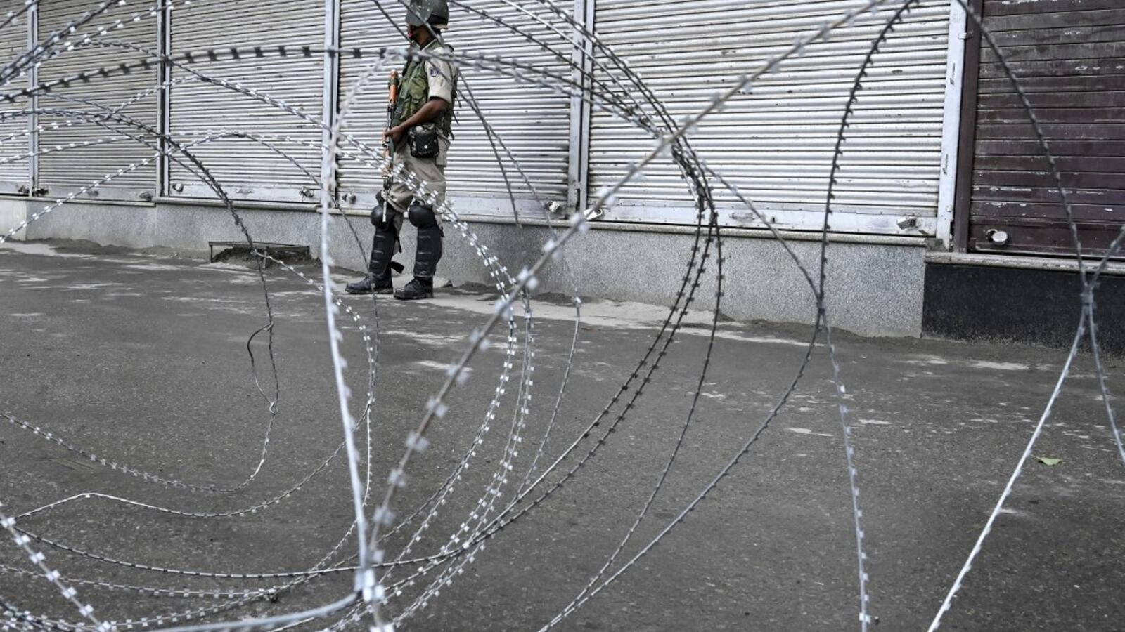 A security personnel stands guard behind a barbed fence wire during a lockdown in Srinagar (AFP)