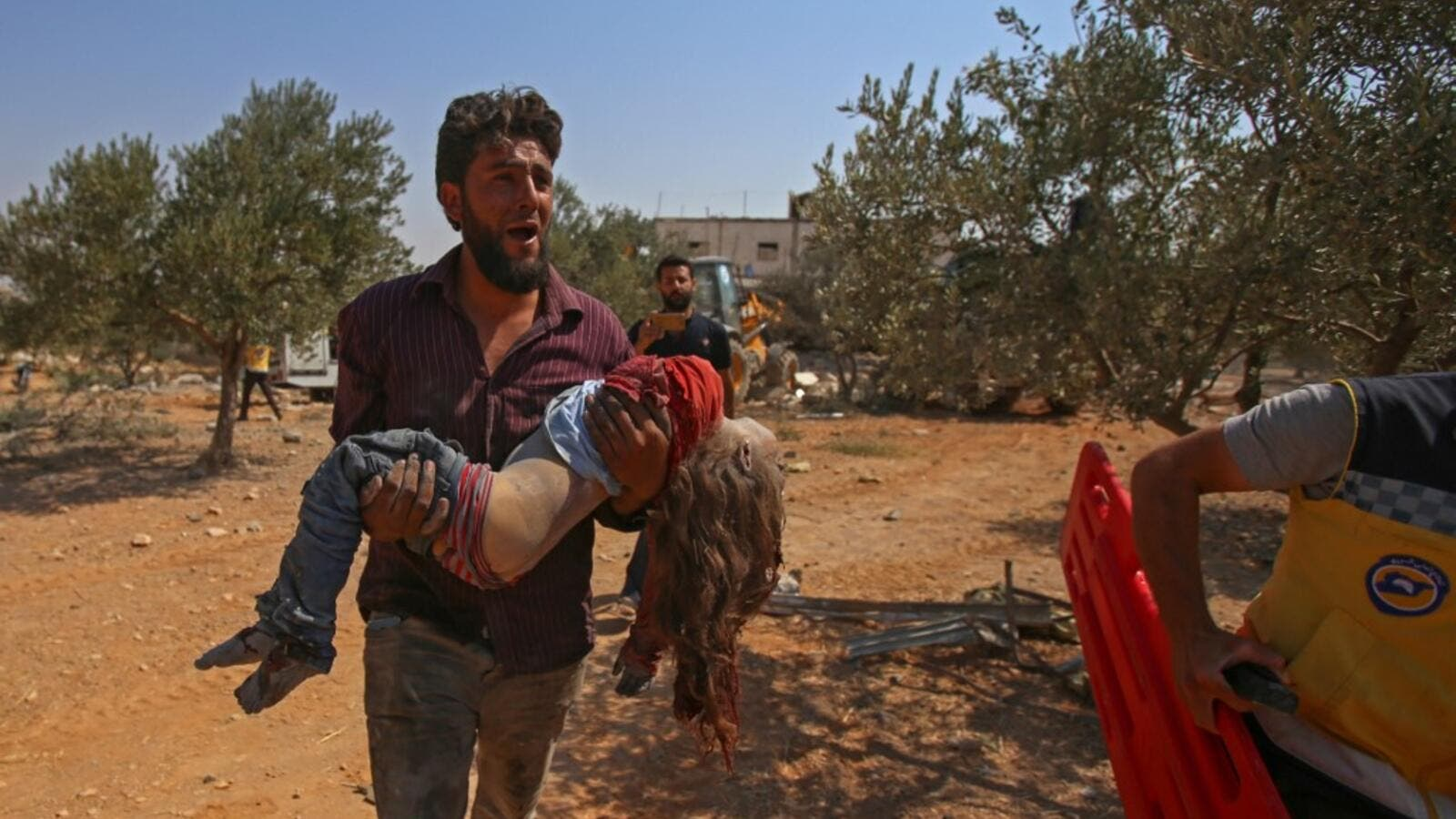 A Syrian carries the body of a child at the site of a reported regime air strike on the village of Deir Sharqi on the eastern outskirts of Maaret al-Numan in Syria's northern province of Idlib on August 17, 2019. (AFP/ File Photo)