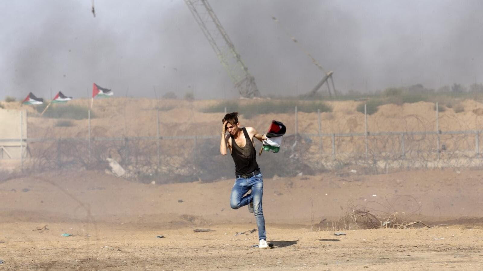 A Palestinian man runs for cover during clashes between Palestinian protesters and Israeli forces across the barbed-wire fence. (AFP/ File Photo)