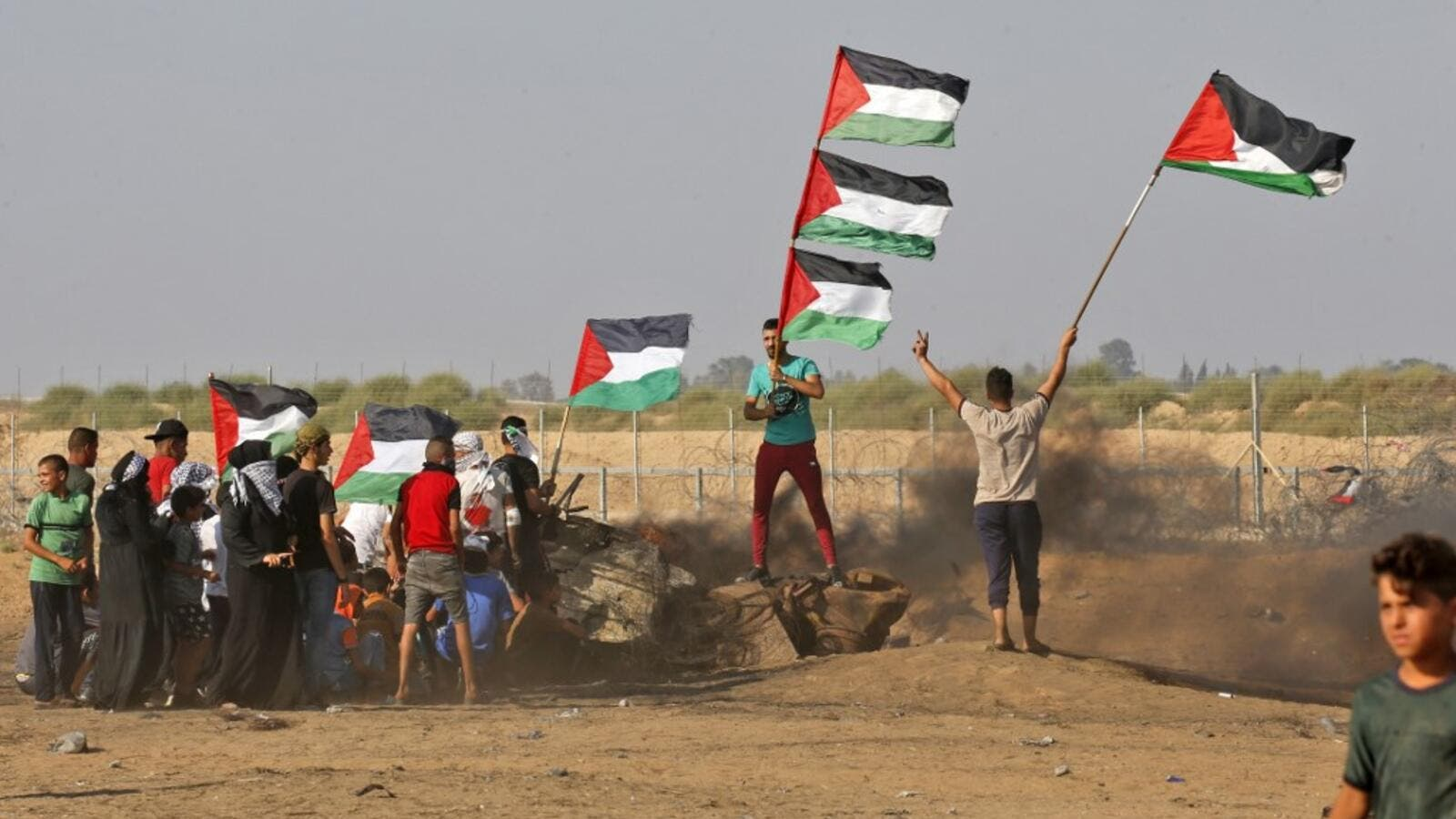 Palestinian demonstrators wave the national flag during clashes between Palestinian protesters and Israeli forces. (AFP/ File Photo)