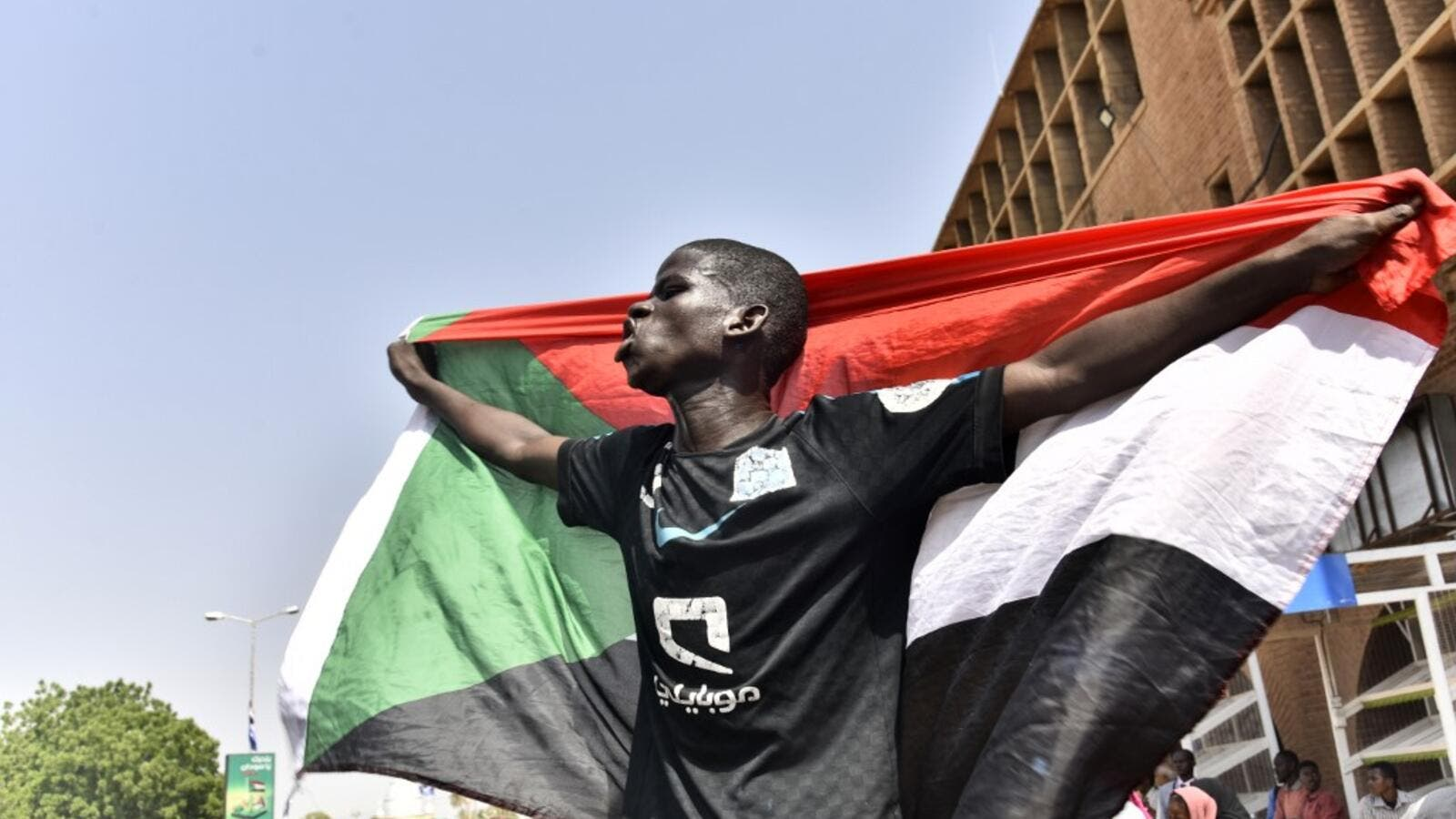 A Sudanese man spreads a national flag in Omdurman as he takes part in a rally in solidarity with Ahmed al-Kheir, a young Sudanese who died in custody after his arrest in January on allegations of organising anti-Bashir protests, on August 28, 2019. (AFP/ File Photo)