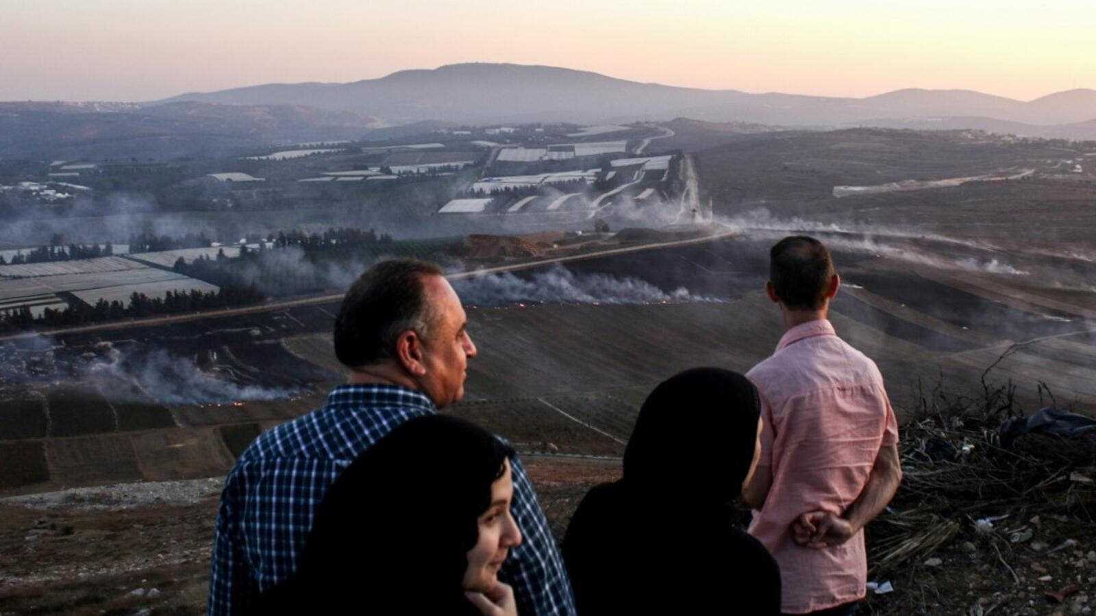 People watch as fires blaze along the Lebanese side of the border with Israel in the Lebanese village of Maroun al-Ras (AFP)