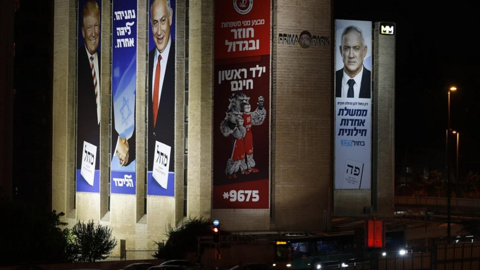 "Israeli election banners and advertising hanging from a building in Jerusalem, (L to R) for the Likud party showing US President Donald Trump shaking hands with Likud chairman and Prime Minister Benjamin Netanyahu with a caption in Hebrew reading ""Netanyahu, in another league""; an advertisement for Hapoel Jerusalem Basketball Club; and for the ""Blue and White"" (Kahol Lavan) electoral alliance showing the face of retired general Benny Gantz and a caption in Hebrew reading ""only with the Blue and White will c"