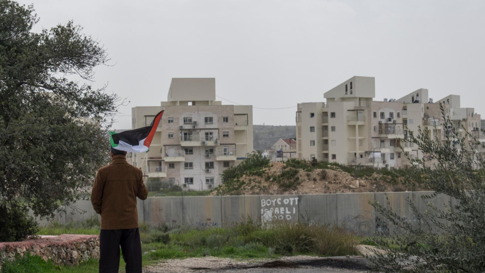 A Palestinian protester stands near the West Bank Barrier holding a flag as a form of protest in Bilin, West Bank, Palestine. (Shutterstock/ File Photo)