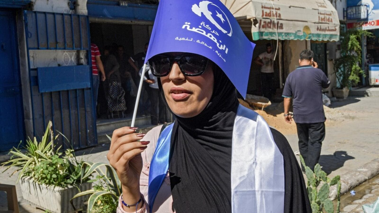 A woman walks holding up a flag of the Islamist-inspired Ennahda party while campaigning in the upcoming upcoming legislative elections in the capital Tunis on October 1, 2019. (FETHI BELAID / AFP)