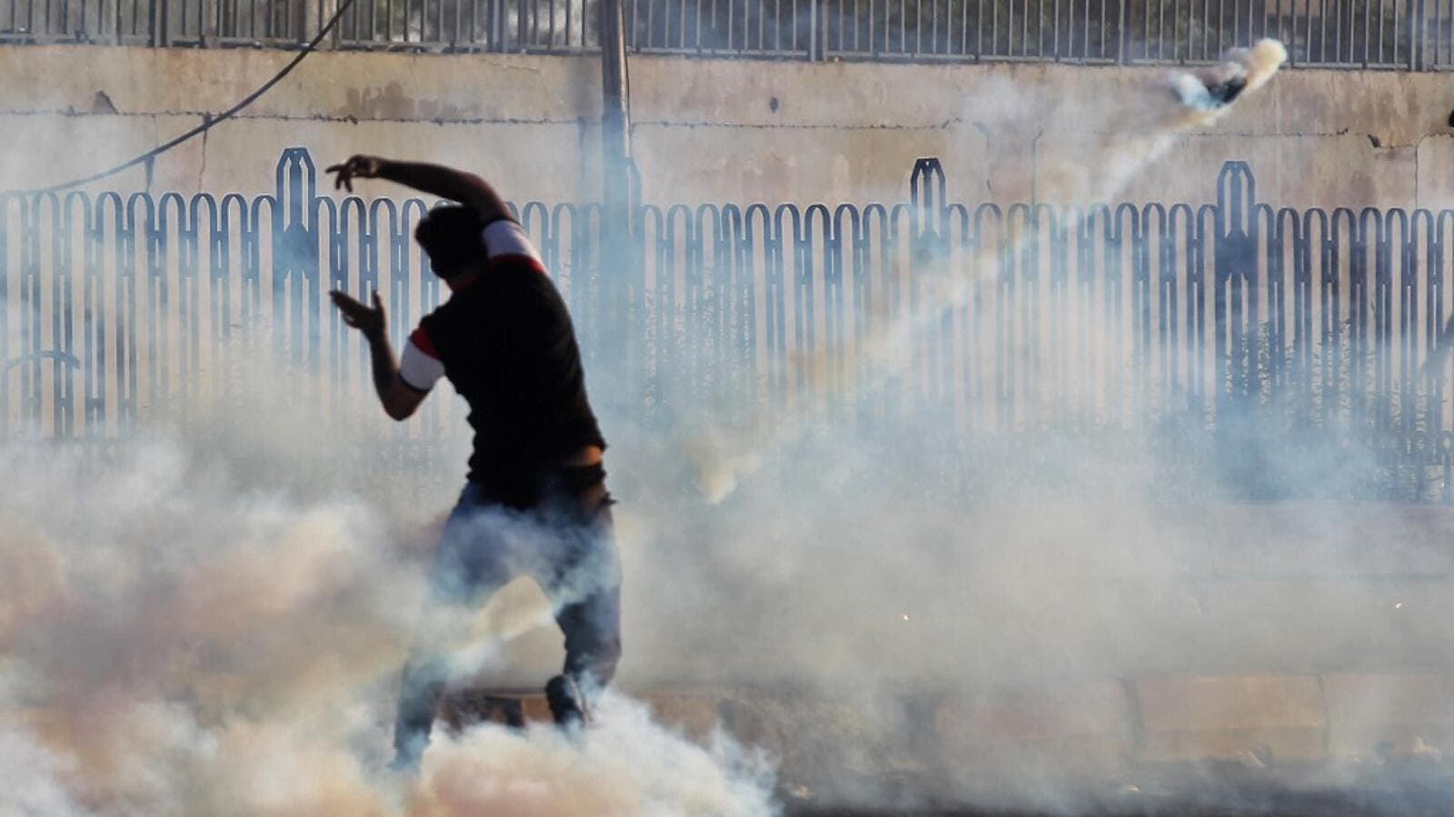 An Iraqi demonstrator gestures amidst smoke from burning tyres and tear gas during a demonstration against state corruption, failing public services and unemployment, in the Iraqi capital Baghdad on October 5, 2019. (AFP/ File Photo)