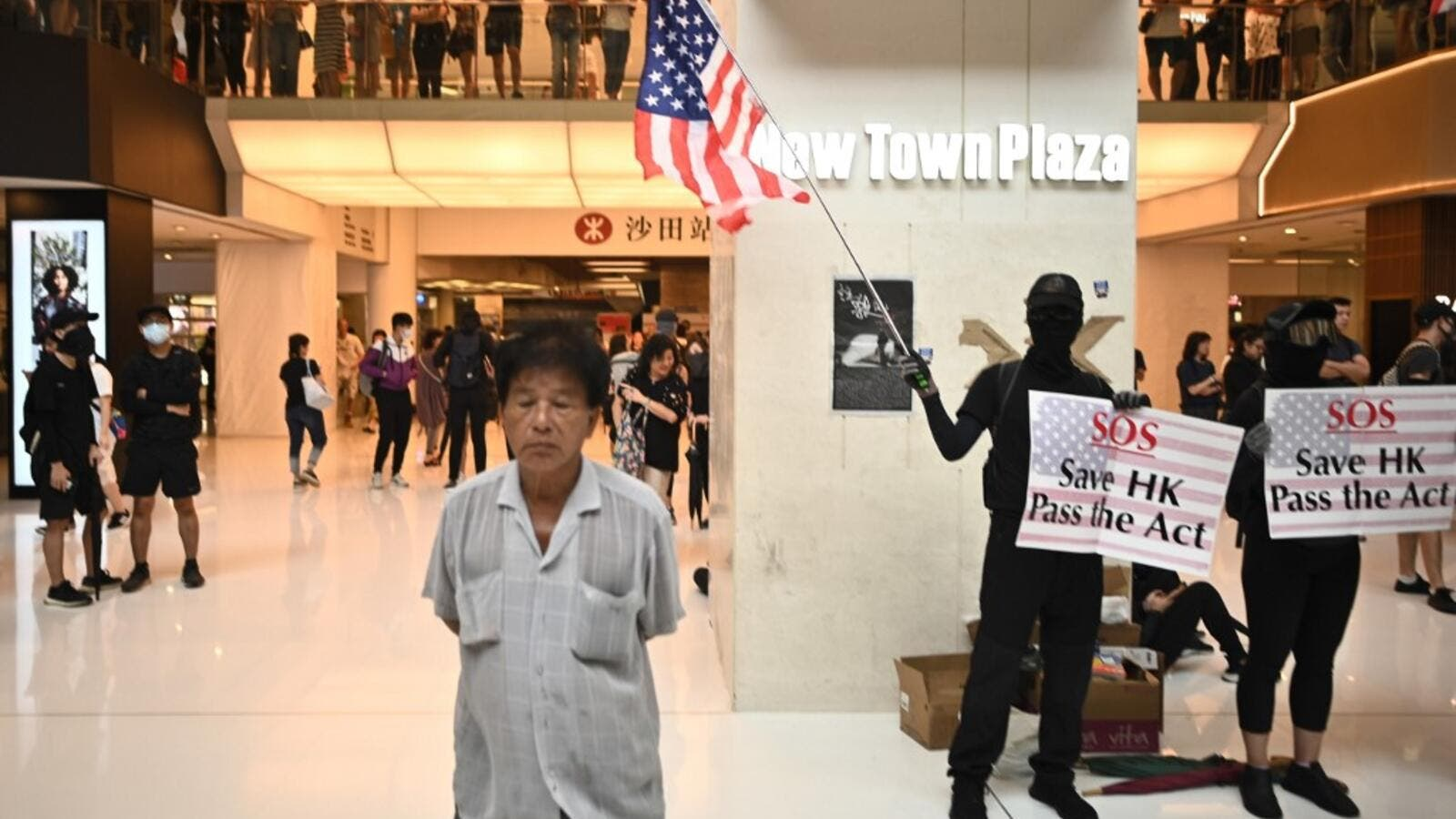 A man (L) walks past a person waving the US flag and holding a sign to rally for the US Congress to pass the Hong Kong Human Rights and Democracy Act, during a flash mob rally inside a shopping mall in the Sha Tin district in Hong Kong on October 13, 2019. (AFP/ File Photo)