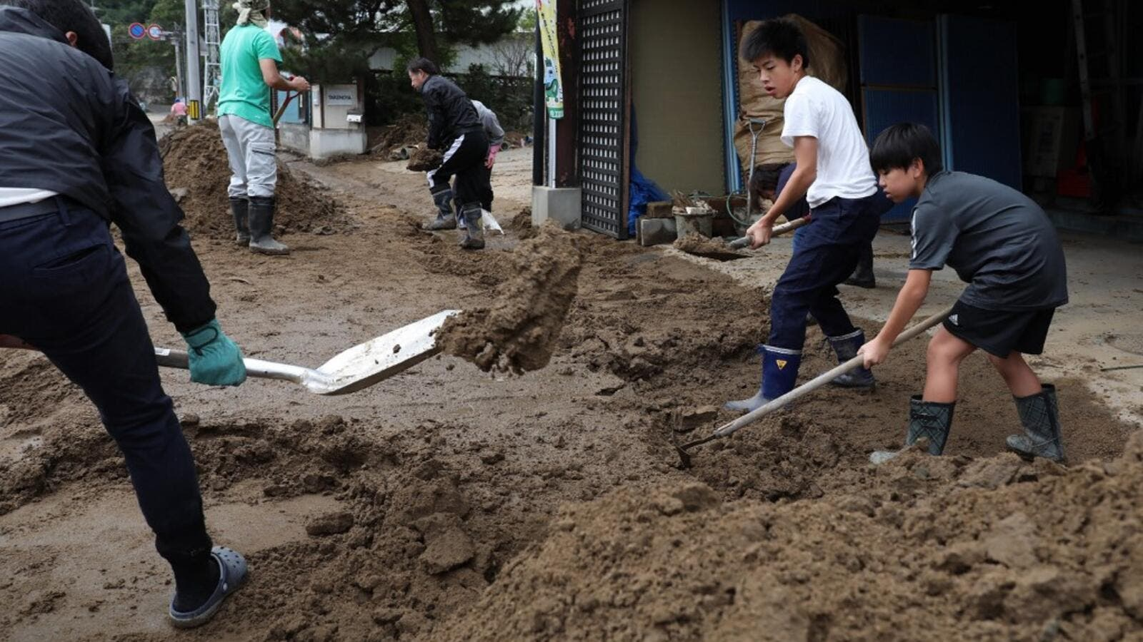 Residents clear mud from a street at the flooded area in Marumori, Miyagi prefecture on October 14, 2019, in the aftermath of Typhoon Hagibis. Tens of thousands of rescue workers were searching for survivors of powerful Typhoon Hagibis, two days after the storm slammed into Japan, killing at least 35 people. (Jiji Press / AFP)