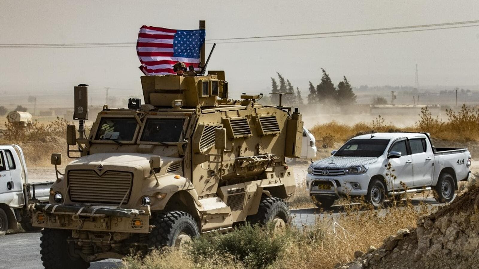 In this file photo taken on October 6, 2019 a US soldier sits atop an armoured vehicle during a demonstration by Syrian Kurds against Turkish threats next to a base for the US-led international coalition on the outskirts of Ras al-Ain town in Syria's Hasakeh province near the Turkish border. (AFP/ File Photo)